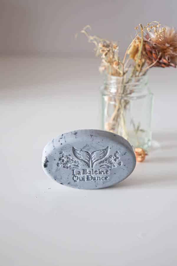 savon naturel au charbon végétale bio posé devant un pot de fleur