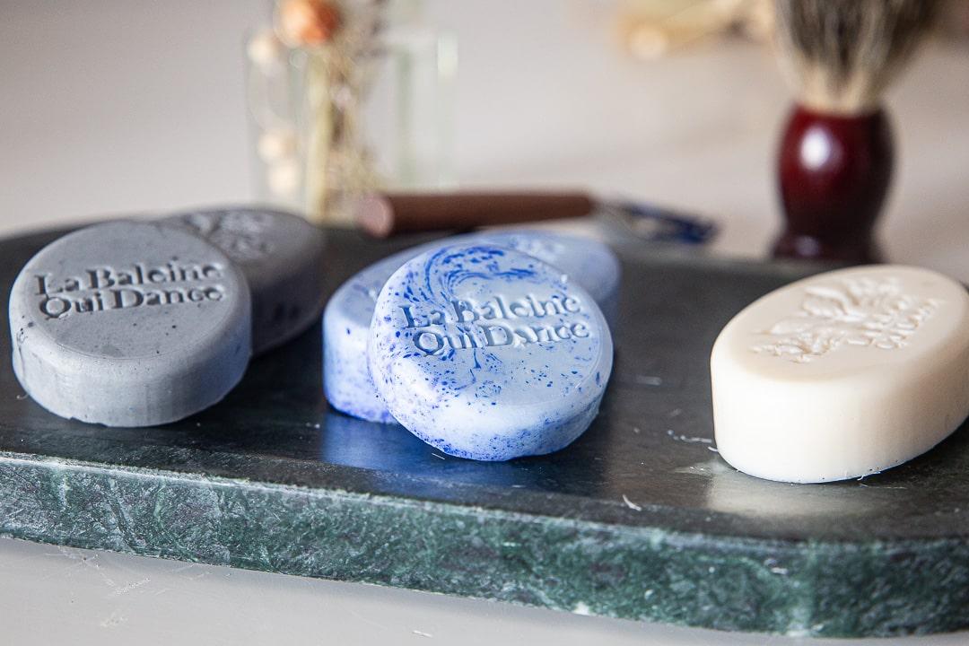 shampoing et cosmétique solide posés sur un plateau en marbre