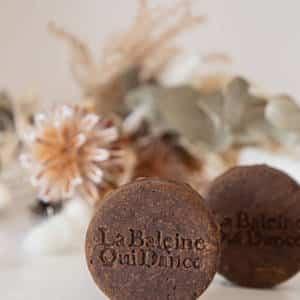 2 shampoings solides bio shikakai & ricin sur une table avec des fleurs